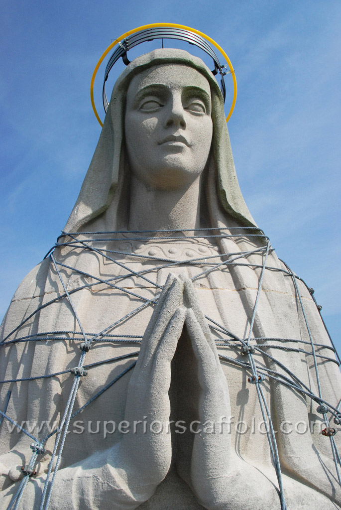 Guy-Wire all over the statue of Mother Mary